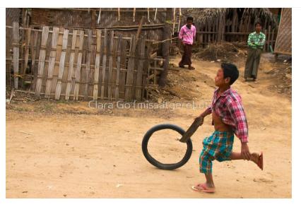 Foto en Jpg descarregable per a us personal - Un nen jugant amb una roda a Myanmar